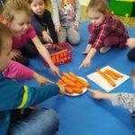 Dzieci siedzą w kręgu wokół talerza z marchewkami