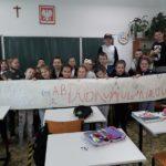 Uczniowie klasy II b i transparent promujący ksiażkę Zaczarowana zagroda