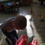 Chłopczyk wrzuca woreczek do koszyka