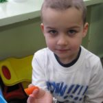 Chłopczyk je marchewkę
