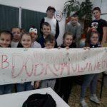Uczniowie klasy II b i transparent promujący książkę Zaczarowana zagroda