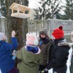 uczniowie dokarmiają ptaki zimą