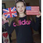 Uczennica trzyma narysowane flagi Anglii i Stanów Zjednoczonych