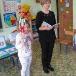 Bibliotekarka opowiada o książkach i dziewczynka trzyma kukiełkę Pinokia